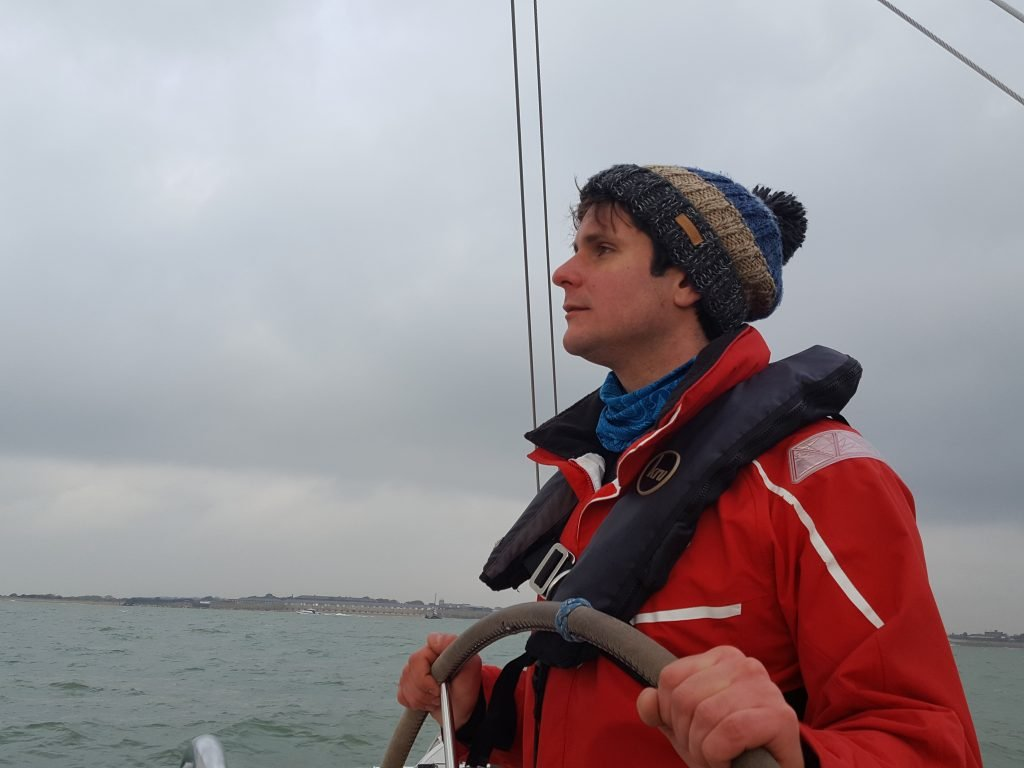 a man wearing the best sailing hat on a cloudy day out sailing