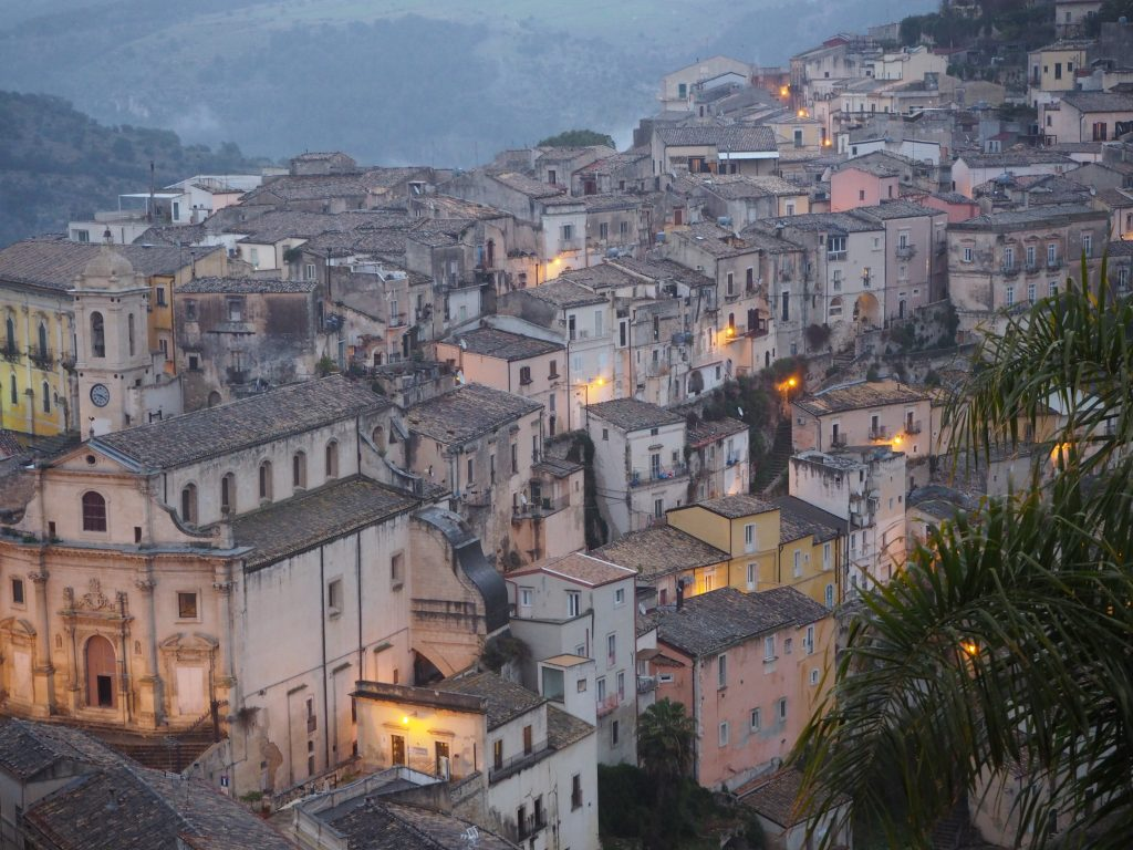 A view of Ragusa Ibla as the light is fading, with golden street lamps casting light