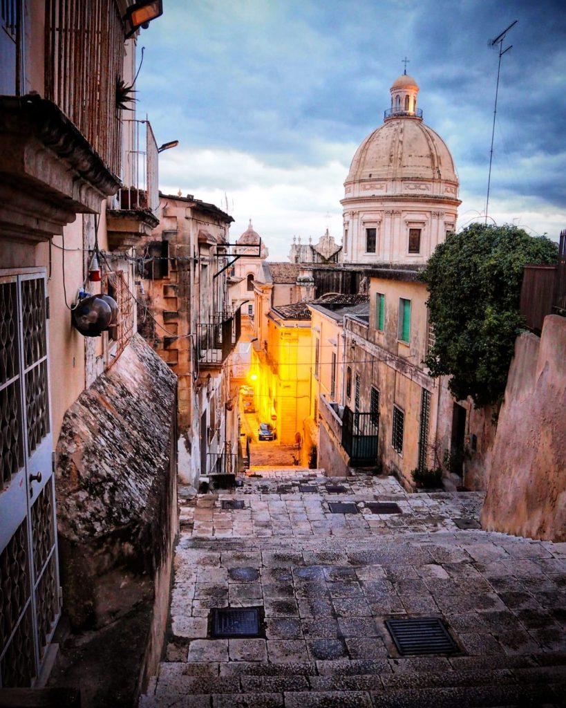 An alley way walk lit up by night lights in Ragusa Ibla