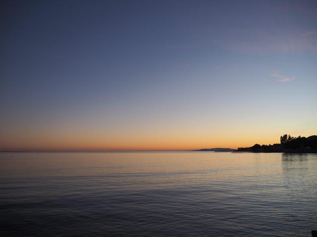 the view of the sunset across the ocean in sant carles de la rapita