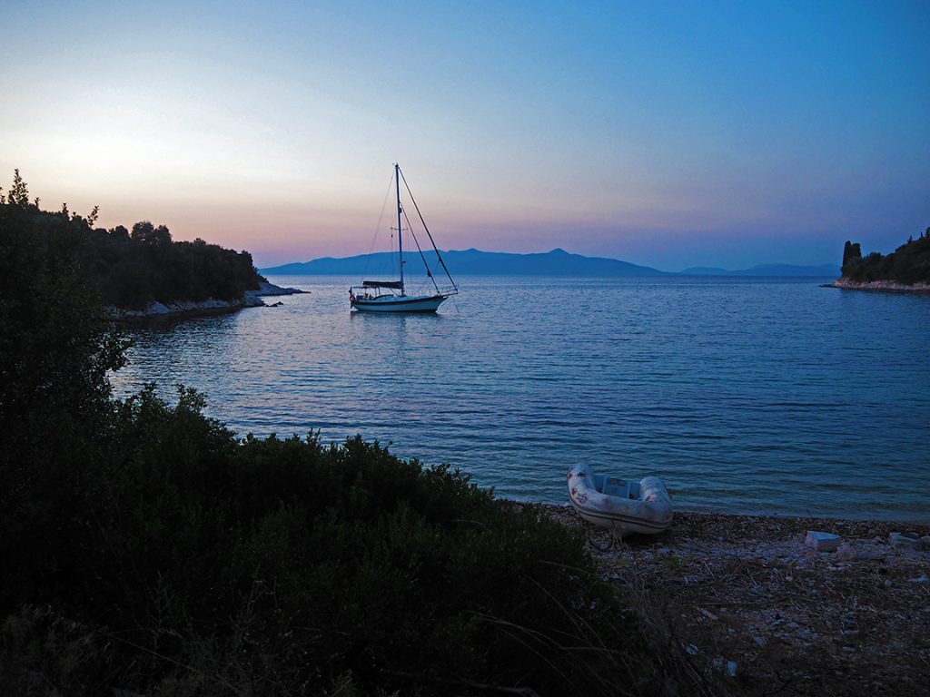 a sailboat in a pretty bay at sunset