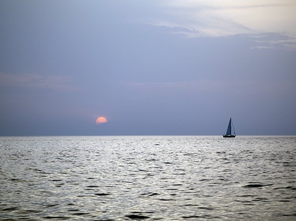 A sailboat at sea with the sun setting behind it