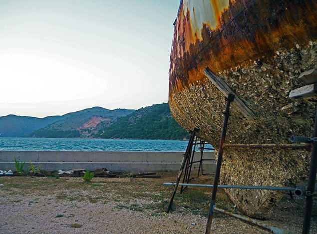 A rusty old boat in an abandoned marina which is what happens when you don't have enough money to live on board a sailboat