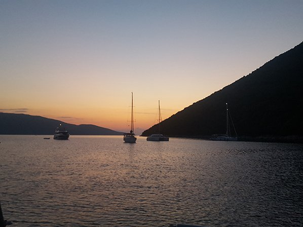 An anchorage in Antisamos with the sun setting behind the mountains