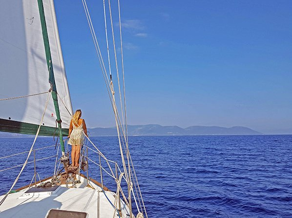 Girl on bow sprit of sailing boat