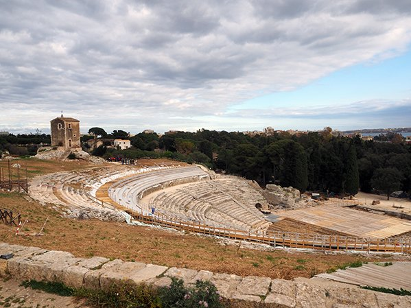 The Greek theatre in Syracuse's archaeological park and a moody, cloud filled sky