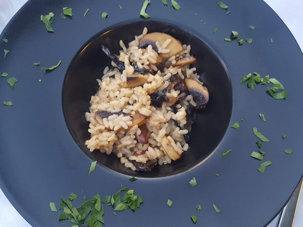 A black plate full of luxury mushroom risotto