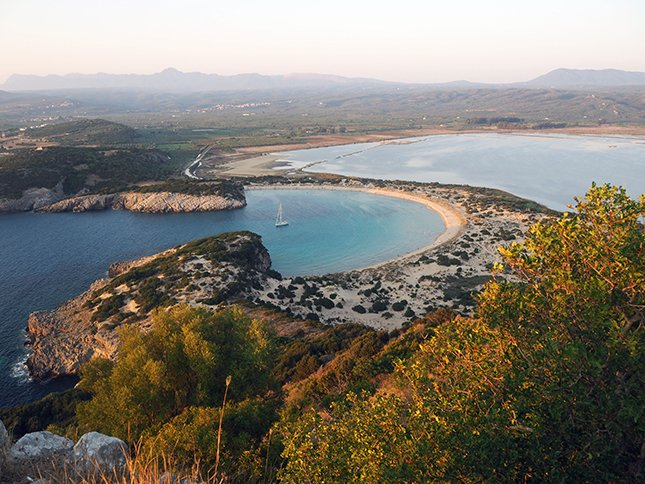 A view of a horseshoe shaped beach in Greece taken by a couple that are living on a sailboat