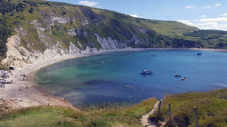 The view over Lulworth Cove bay with cliffs and sea