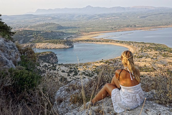 A GIRL LOOKING AT THE VIEW OVER PILOS IN GREECE