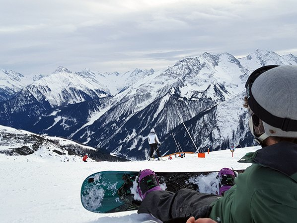 rental ski equipment that isn't included in a ski trip packing list includes a snowboard like the one this man has