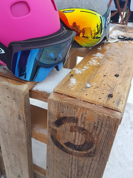 Two helmets and ski goggles in the snow