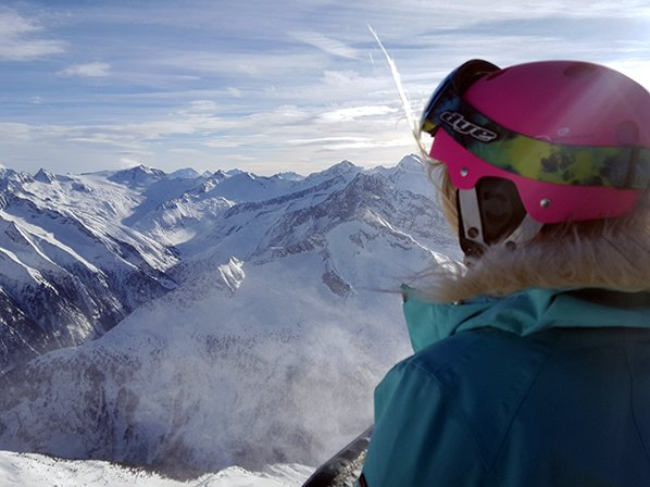 A girl wearing a ski helmet from her ski trip packing list looking out over snowy mountains