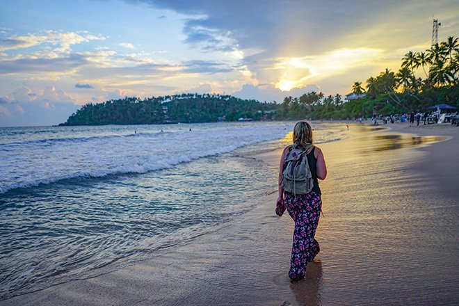 A girl going for a sunset walk along the beach in mirissa
