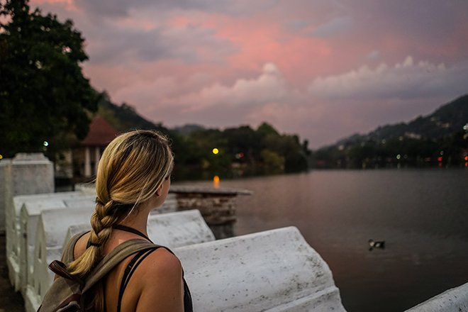 A girl looking at the sunset over kandy lake in sri lanka