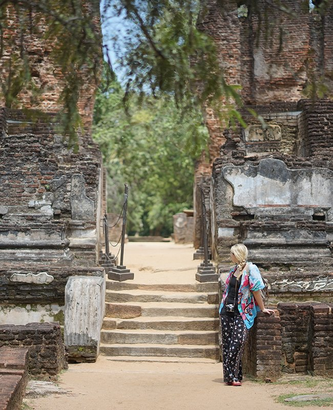 a girl standing beside an ancient temple on her 5 days in sri lanka trip