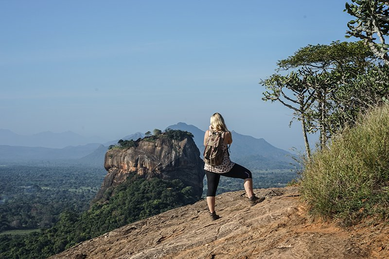 A GIRL TAKING PICTURES OF THE VIEW OF SIGIRIYA ROCK