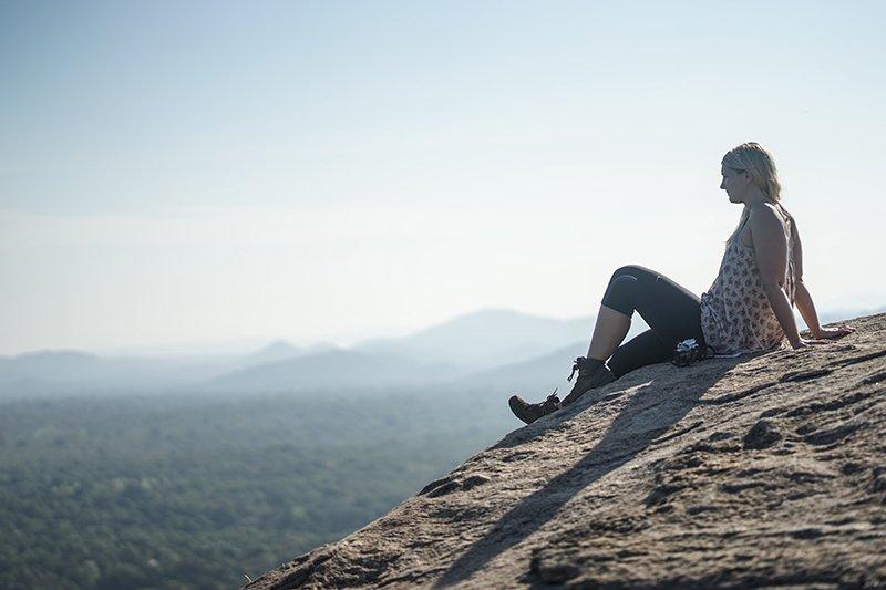 A GIRL SAT RELAXING ON PIDURANGALA ROCK, one of the top things to do in sigiriya