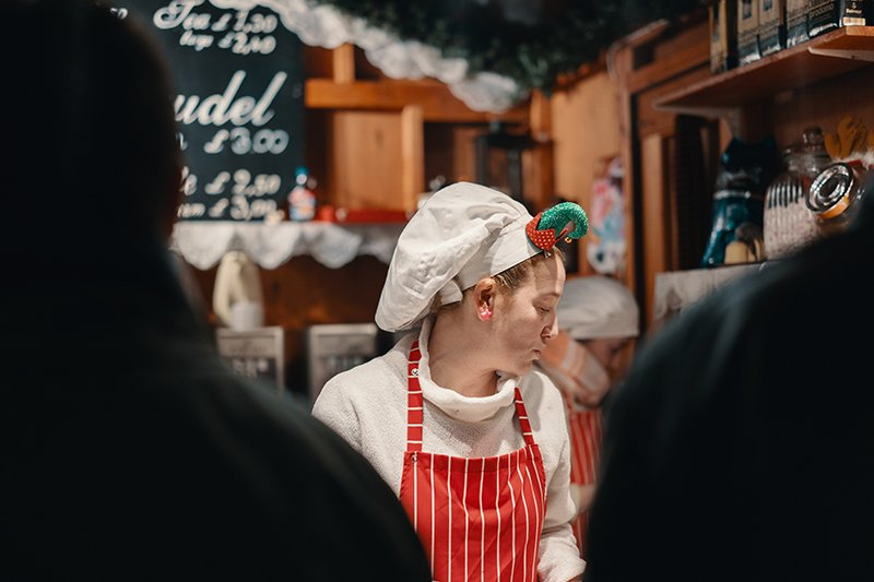 A girl serving food at one of the best christmas markets in hampshire