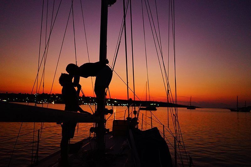 A COUPLE KISSING ON THEOR KADEY KROGEN 38 SAILBOAT