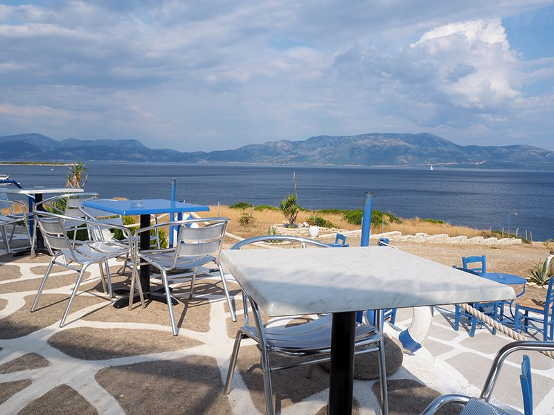 Tables and chairs outside the windmill bar on Kastos island in Greece