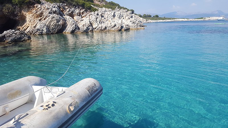 A dinghy floating in clear blue water in Kastos anchorage