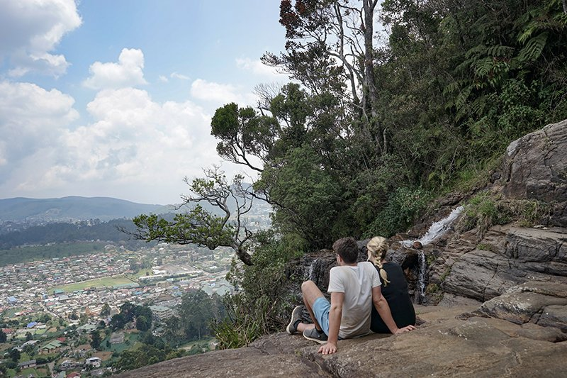 A COUPLE SAT ON THE TOP OF LOVERS LEAP WATERFALL IN NUWARA ELIYA