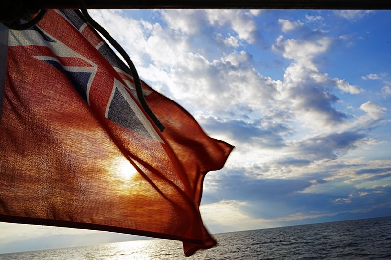 THE ENGLISH FLAG FLYING FROM THE BACK OF A SAILBOAT IN GREECE