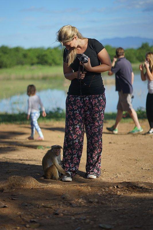 A monkey clinging onto a girls leg in udawalawa national park in sri lanka