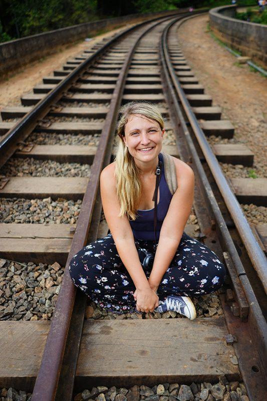 A GIRL SITTING ON THE RAILWAY TRACKS OF NINE ARCH BRIDGE IN ELLA