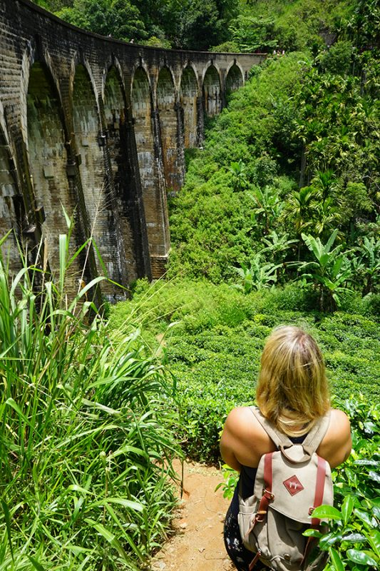 A GIRL STANDING IN TEA PLANTATIONS LOOKING AT NINE ARCH BRIDGE IN ELLA