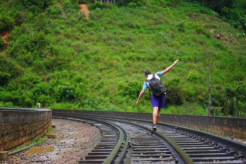 A BOY WALKING ALONG THE RAILWAY TRACKS OF NINE ARCH BRIDGE IN ELLA
