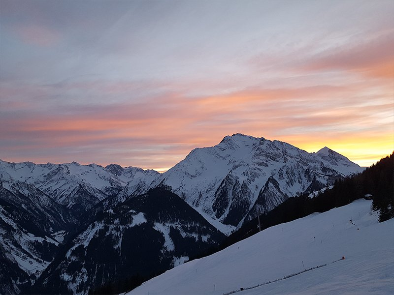 THE SUNSET OVER THE SNOW COVERED MOUNTAINS OF A BUDGET SKIING RESORT