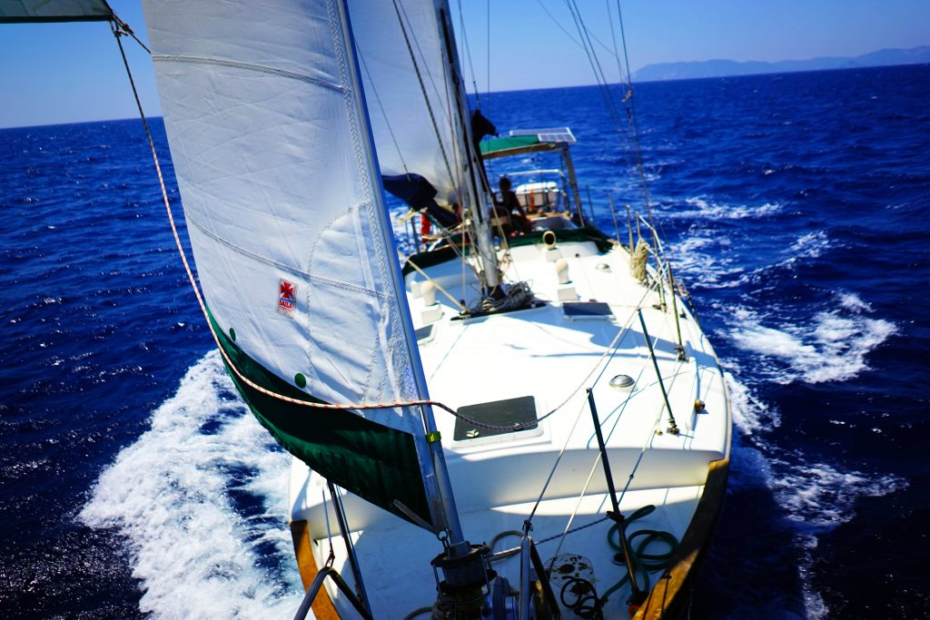 a sailboat sailing with happy crew because their covered by insurance for sailing!