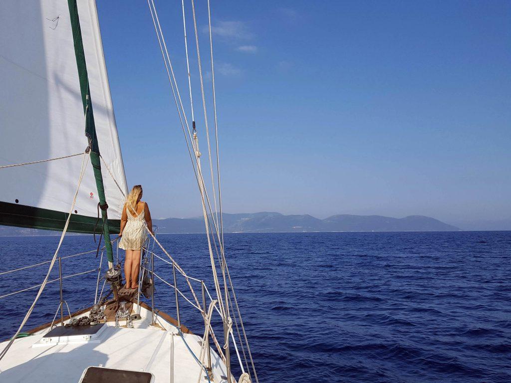 a girl wearing sailing clothes on a sailboat at sea