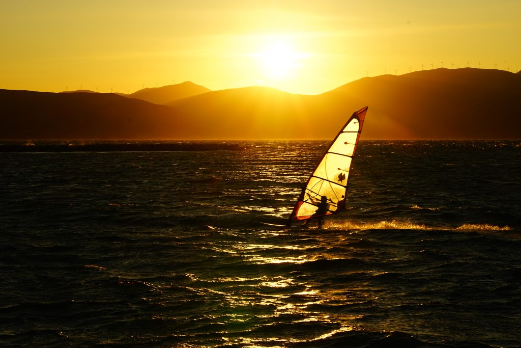 A windsurfer surfing as the sun sets behind him