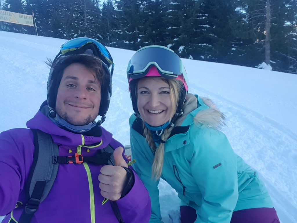 A couple smiling in the snow in all their ski gear