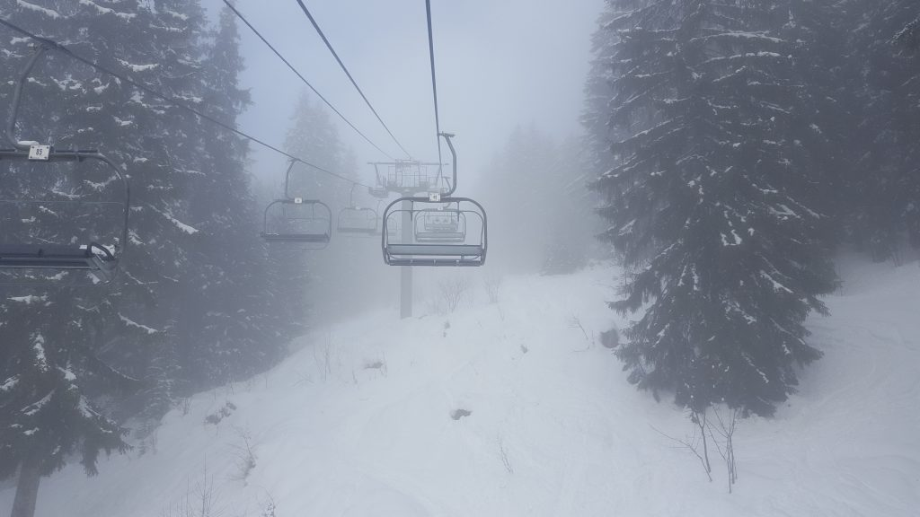 A SKI LIFT GOING UP IN THE SNOW