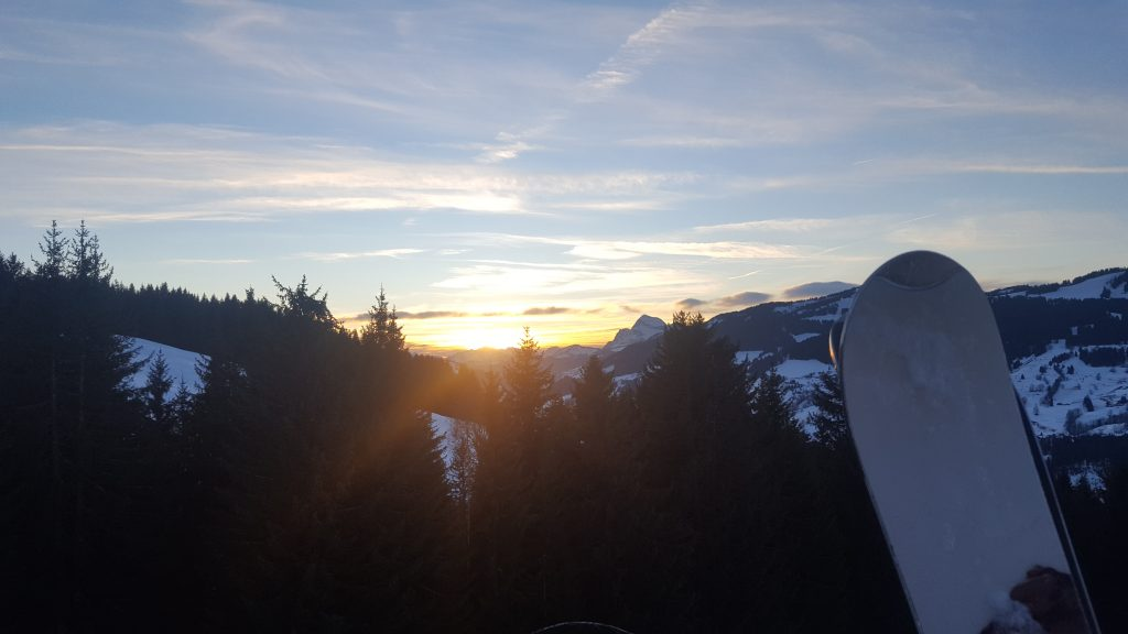 THE SUN SETTING IN THE MOUNTAINS WITH SKIS IN THE FOREGROUND