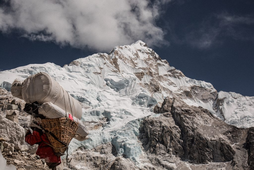 A SHERPA CARRYING A HUGE BUNDLE UP A MOUNTAIN PATH IN THE HIMALAYAS