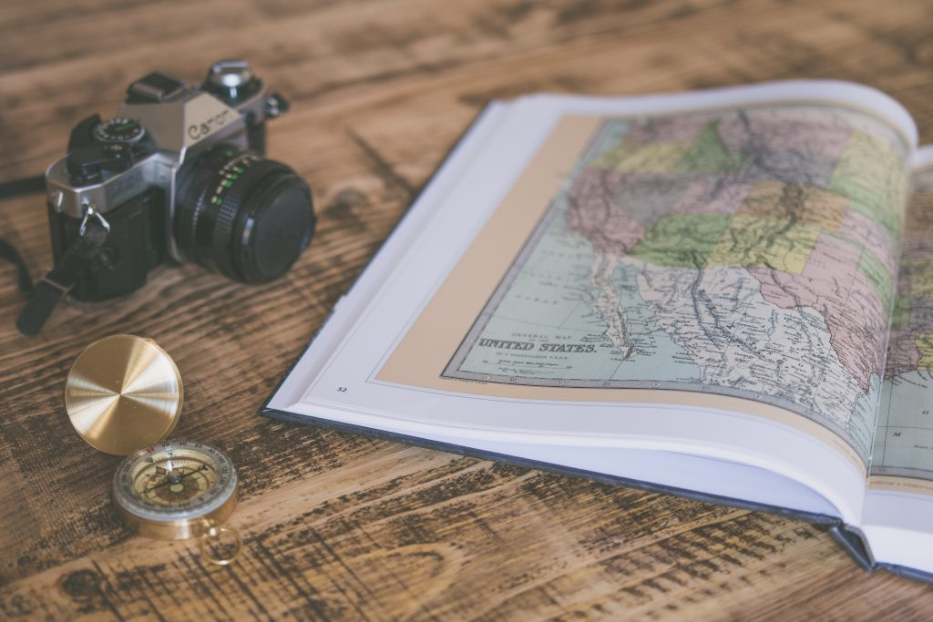 A SMALL TRAVEL CAMERA FOR BLOGGING MAKES THE BEST ONE, AS SEEN IN THIS PHOTO OF A SMALL CAMERA NEXT TO A MAP