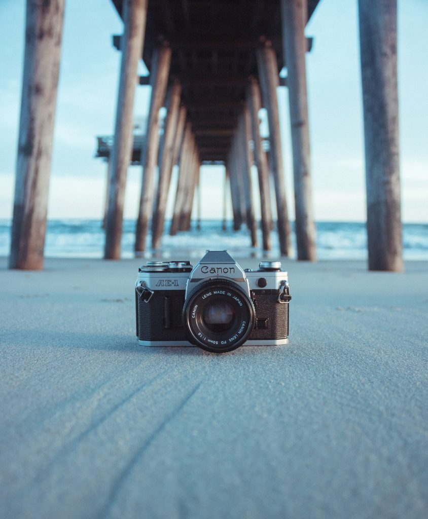 the best camera for blogging sat in the sand under a pier