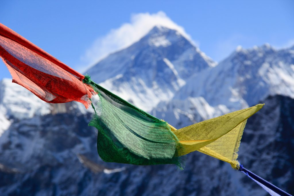 PRAYER FLAGS HUNG HIGH UP IN THE NEPAL MOUNTAINS BY BACKPACKERS