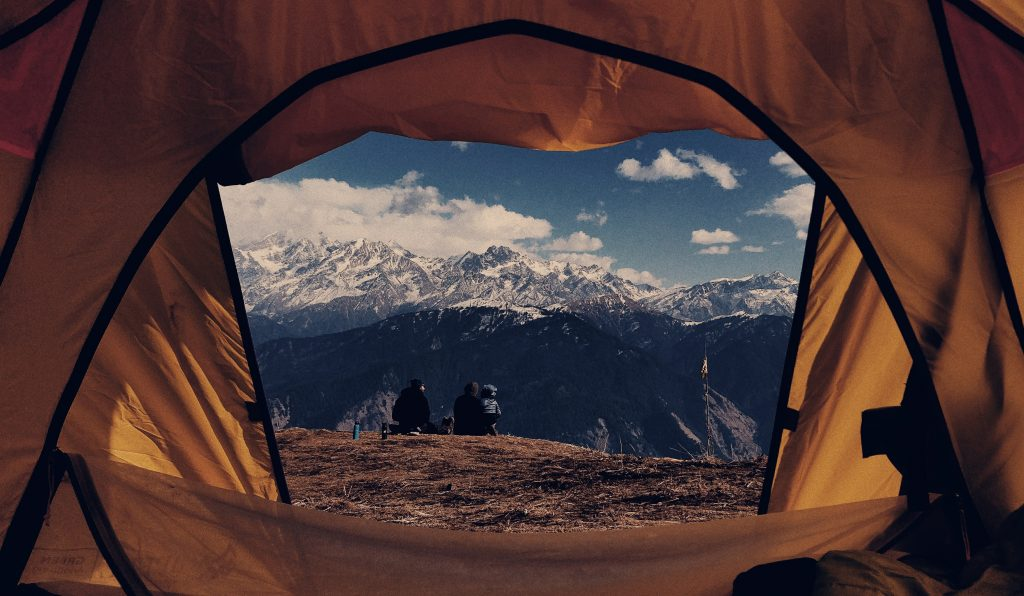 A TENT WITH AN OPEN DOOR LOOKING OUT ONTO SOME MOUNTAINS IN NEPAL