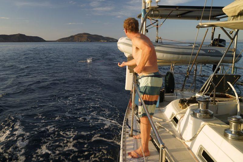 a man fishing from his sailboat