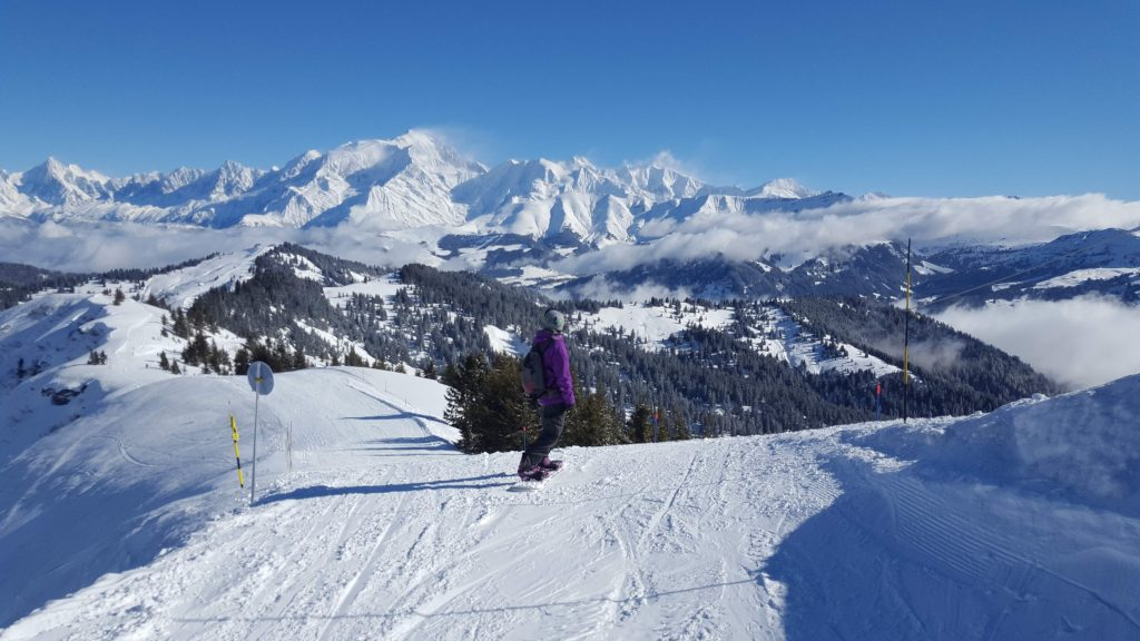 a snowboarder at the top of a piste in combloux with the incredible mountains behind