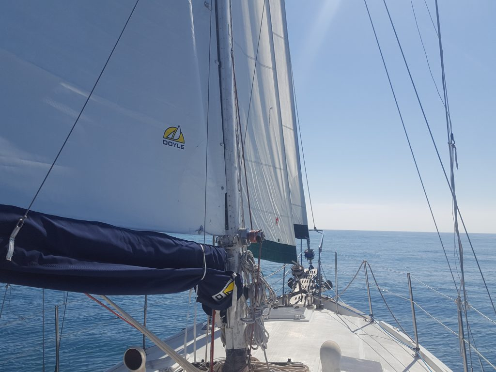 a sailboat with three sails, making the cost of boat ownership more expensive