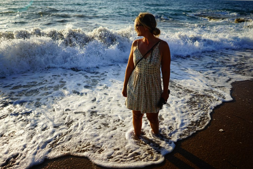 A girl standing on a beach with the tide coming in around her feet