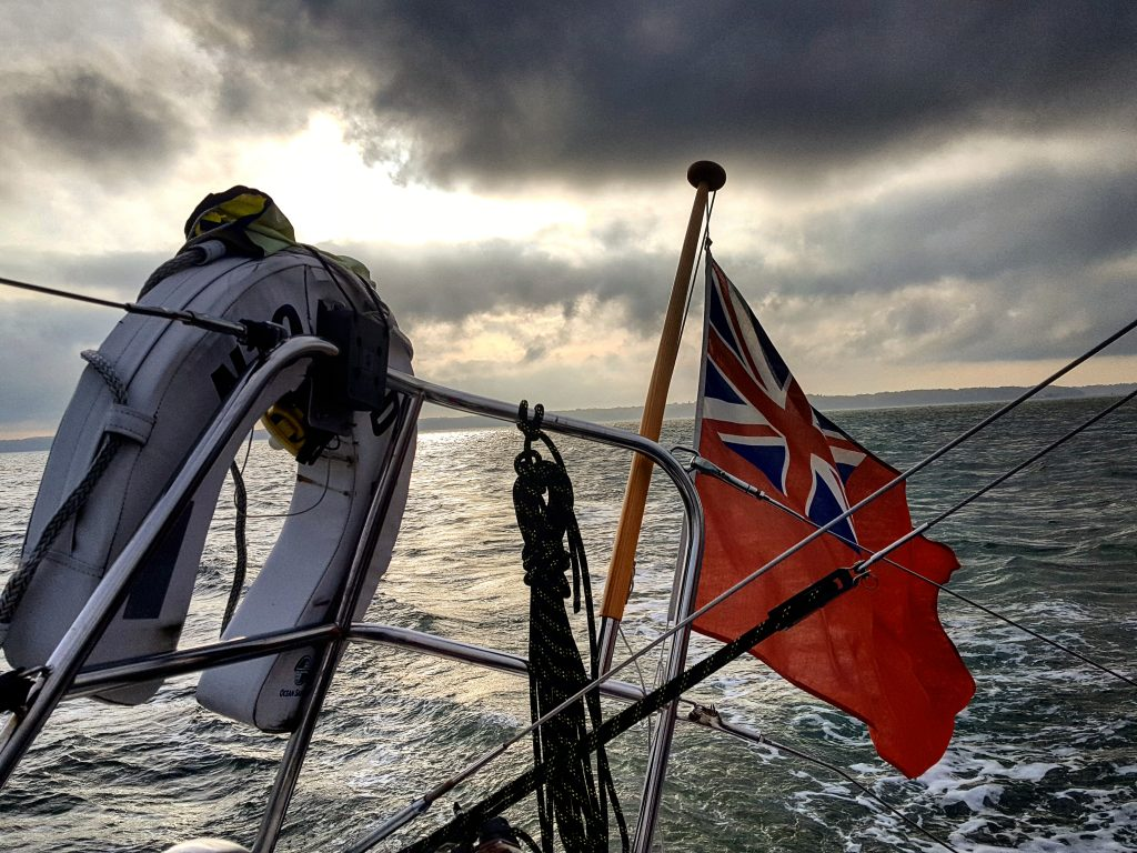 the back of a sailboat on a moody day, with rain clouds threatening and the sun just breaking through