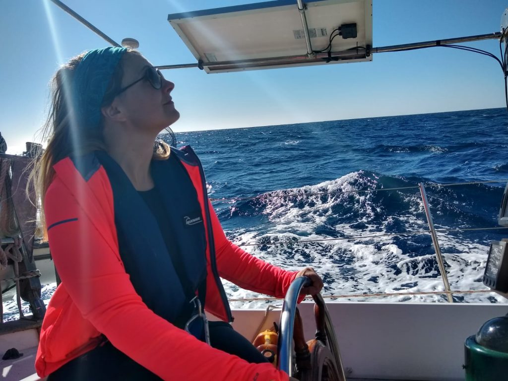 a girl at the helm of a sailboat in greece at the start of her life at sea